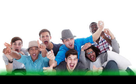 Young men screaming at the tv in joy. Going crazy.