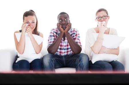 personas viendo tv: Grupo de j�venes de la gente viendo la televisi�n - las dos ni�as llorando, mientras que el hombre se aburre.