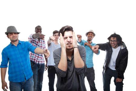 discriminacion: Joven acusado por sus amigos en el fondo blanco