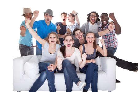 personas viendo television: Grupo de amigos que disfrutan viendo la televisión en el fondo blanco