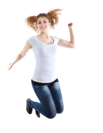exuberance: Beautiful Casual Woman Jumping In Joy On White Background