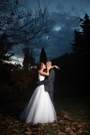 Portrait Of Young Married Couple Kissing Outdoors photo