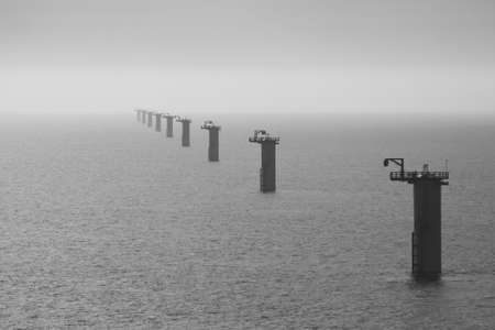 Long row of wind turbine foundations at an offshore windfarm under construction off the Norfolk Coast, North Sea photo