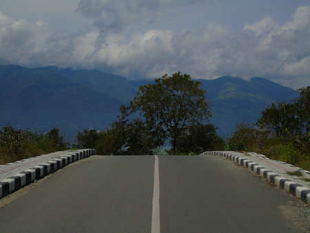 the view of the uphill road that is immediately visible is connected to trees and mountains.