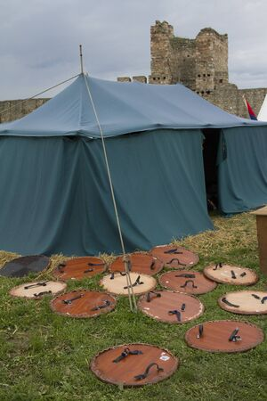 a scene from medieval times, shields in front of a tent Redakční