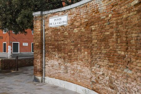 A curved old wall of red bricks, on the streets of Venice
