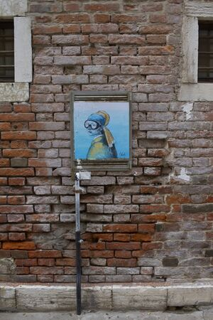 Artwork in front of a red brick wall, on the streets of Venice Redakční