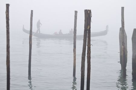 Gondolas in Venice surrounded by fog in the early winter morning Redakční