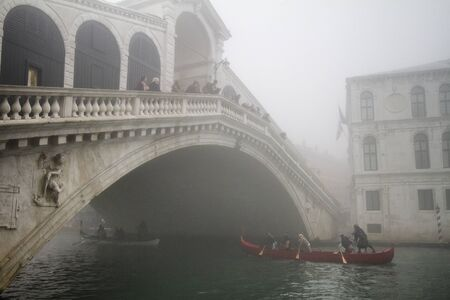 Rialto Bridge In Venice surrounded by fog with a gondola passing under it