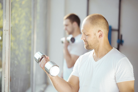 only the biceps: Satisfied young strength man lifting dumbbell in a gym