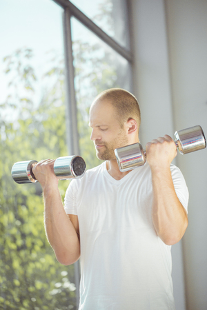 only the biceps: Satisfied young strength man lifting dumbbell at home