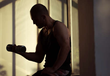 free weights: Man lifting free weights in the gym - silhouette Stock Photo