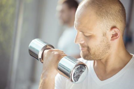 only adult: Satisfied young strength man lifting dumbbell in a gym