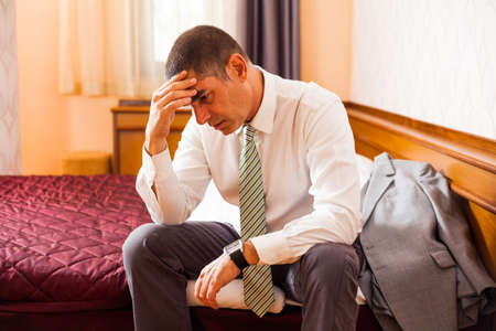 Worried businessman sitting in hotel room and thinking photo