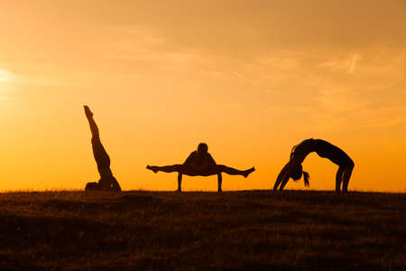 practicing: Girls practicing yoga in sunset