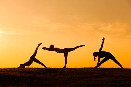 Silhouettes of girls practicing yoga in sunset Фото со стока