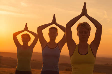 practicing: Three girls practicing yoga in sunset Stock Photo