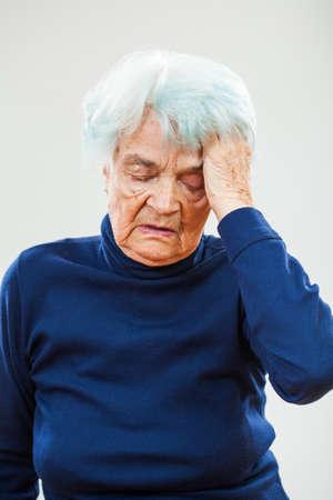 80 plus adult: Senior woman having headache