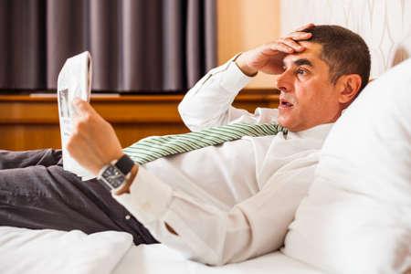 Businessman reading bad news in newspaper photo