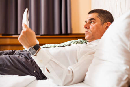 Businessman is resting in bed and reading newspaper photo