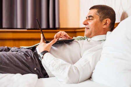net surfing: Businessman lying in bed and surfing the net on laptop