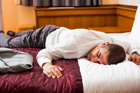 tired businessman: Tired businessman is sleeping on a bed