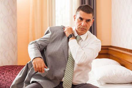 vistiendose: El hombre de negocios se est� vistiendo en la habitaci�n del hotel