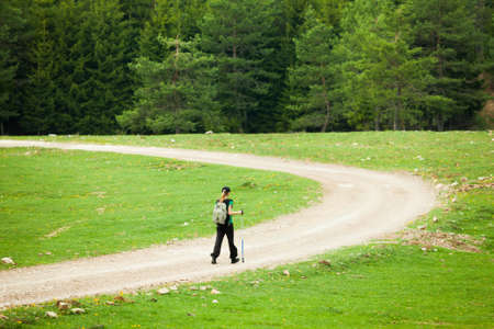 outdoor pursuit: Hiker on road in forest Stock Photo
