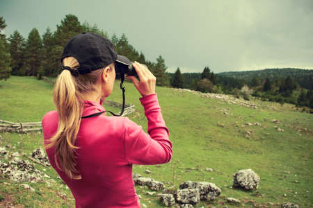 outdoor pursuit: Woman looking through binoculars, intentionally toned