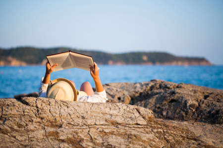 Woman reading a book on the seashore