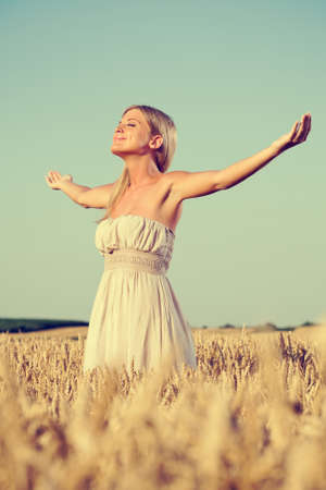 intentionally: Woman meditating in wheat field, intentionally toned Stock Photo
