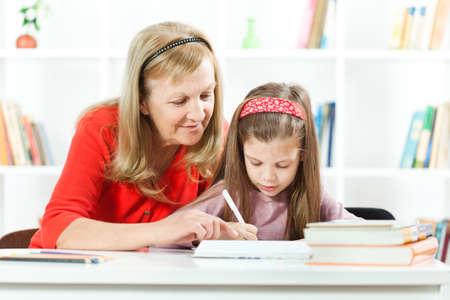 Großmutter helfen ihre Enkelin zu lernen, zu schreiben, Standard-Bild - 38390876