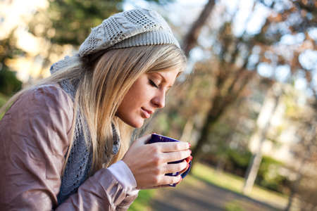 Young woman drinking tea in park photo