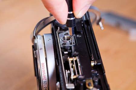 disassemble: Technician repairing old photo camera Stock Photo
