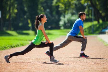 若い夫婦カップルのウォーミング アップのジョギング、ストレッチ体