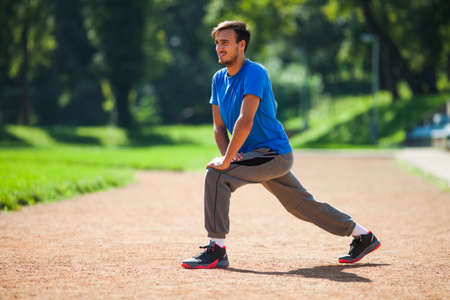 warming up: Young man stretching body, warming up for jogging