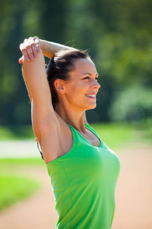 Young woman stretching body, warming up for jogging