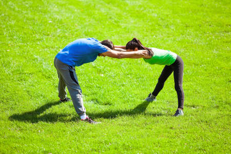 warming up: Young couple stretching bodies, warming up for jogging