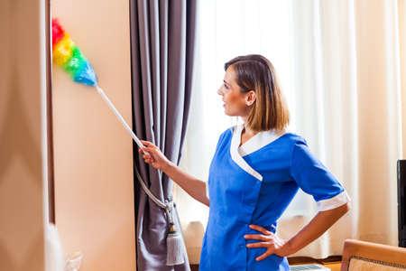 dusting: Hotel maid dusting