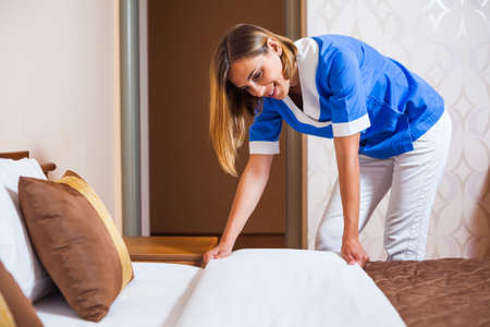 sheets: Maid making bed in hotel room Stock Photo