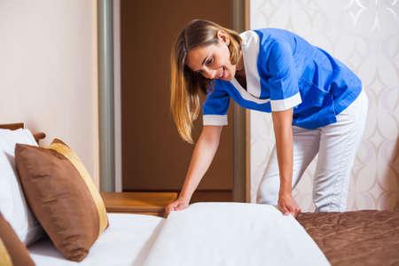 Maid making bed in hotel room Фото со стока - 38721451