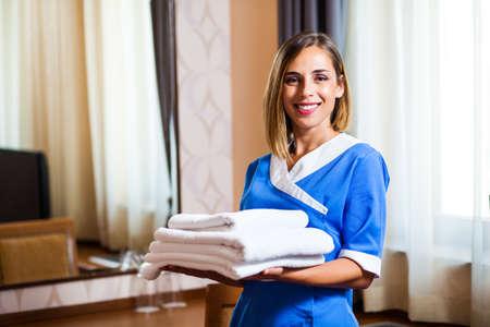Happy hotel maid holding towels in hotel room Foto de archivo