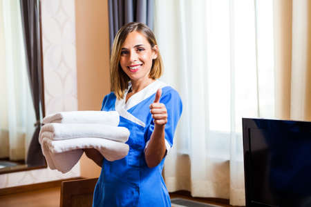 Happy hotel maid holding towels and showing thumb up photo