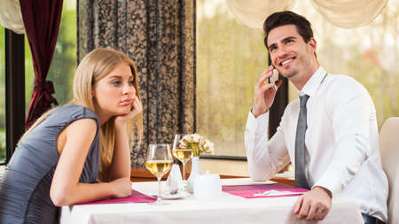Woman is getting bored in restaurant while her boyfriend is talking on the phone
