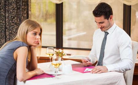 彼女のボーイ フレンドは、sms を入力している間、女性はレストランで退屈させて得ること