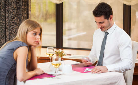 Woman is getting bored in restaurant while her boyfriend is typing sms Foto de archivo