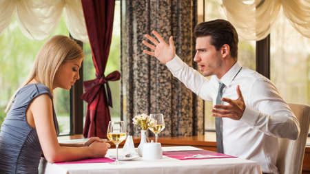 couple talking: Young couple is arguing in restaurant