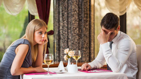 bored face: Young couple is getting bored on first date