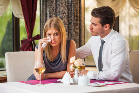 consoling: Young man is consoling his girlfriend at the restaurant Stock Photo