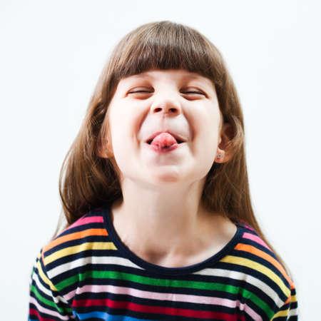 sacar la lengua: Niña que hace la cara Foto de archivo